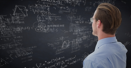 Digital composite of Back of business man looking at navy chalkboard with math doodles Stock Photo