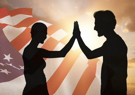 Digital composite of People shadow high fiving against american flag 版權商用圖片