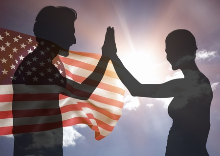 Digital composite of Shadow of people high fiving against american flag and sun