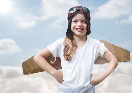 Digital composite of Girl in pilot costume against sky with flare Stock Photo
