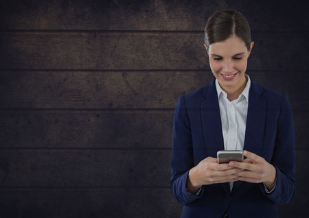 Digital composite of Smiling woman texting against wooden background