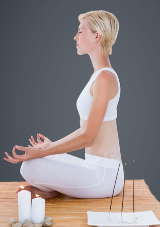 Digital composite of Woman meditating with candles against grey background