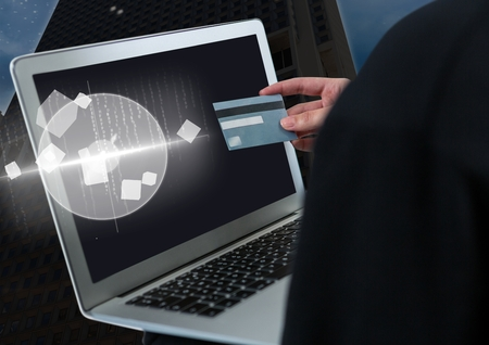 Digital composite of Hacker holding a credit card and a laptop in front of building