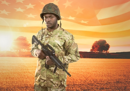 Digital composite of Soldier holding a weapon in front of field