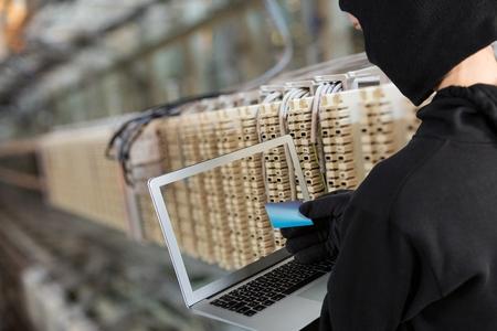 intruder: Digital composite of Hacker using a laptop in a data center