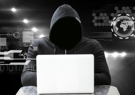 Digital composite of Hacker using a laptop in front of dark background with digital icons