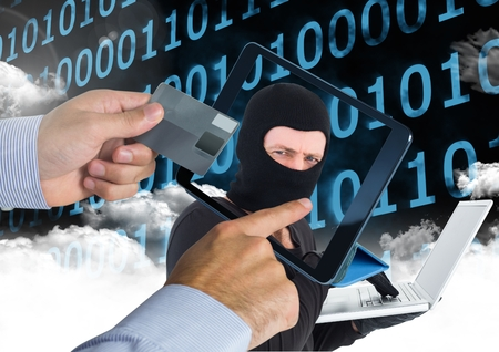 Digital composite of Man using a tablet with hacker head on screen  while holding a credit card