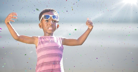 Digital composite of Boy in sunglasses hands out against blurry beach with flare and confetti