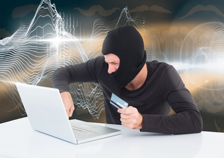 frown: Digital composite of Hacker with a credit card working on laptop in front of digital background