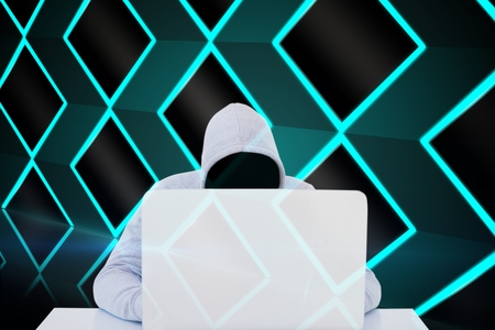 Digital composite of Masked hacker using a white laptop Stock Photo