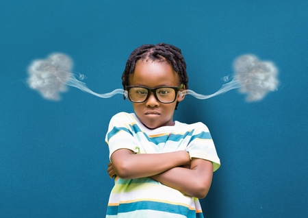Digital composite of anger boy with hands folded and 3D steam on ears. blue background Stock Photo