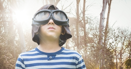 Digital composite of Boy with goggles against blurry trees with flare