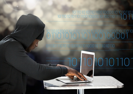 Digital composite of Hacker using a laptop in front of digital background