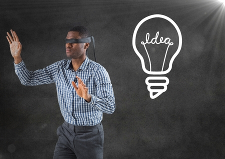 Digital composite of Blindfolded business man against grey wall with flare and white lightbulb graphic Stock Photo
