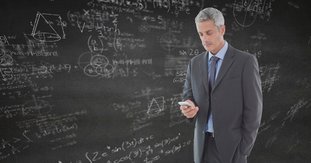 Digital composite of Business man texting against grey wall with math doodles Stock Photo