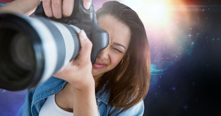 photographing: Digital composite of Photographer taking pictures against galaxy background Stock Photo