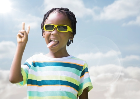 Digital composite of Boy in sunglasses making peace sign against sky with flare Stock Photo