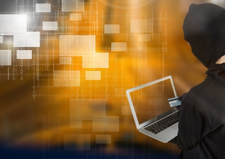 Digital composite of Woman hacker holding a credit credit while using a laptop in front of yellow background