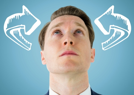 Digital composite of Man looking up at white 3D curved arrows against blue background