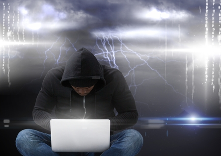 stealer: Digital composite of Hacker seated with cross-legged using a laptop in front of storm background