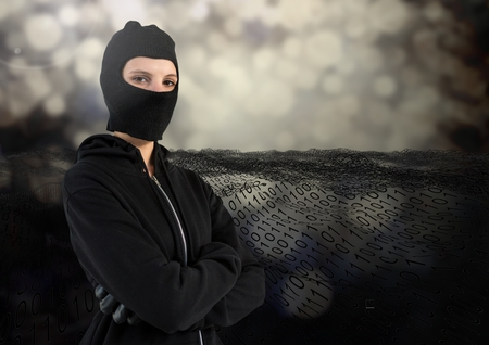 Digital composite of Woman hacker with hood and arms crossed standing on in front of digital background