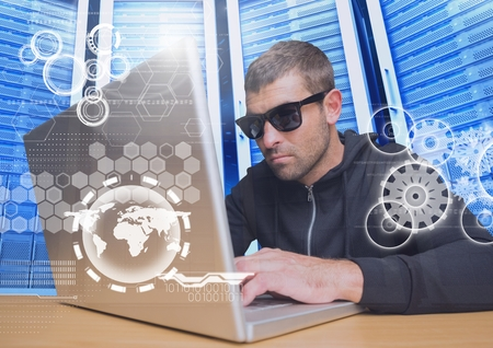 Digital composite of Hacker with sunglasses using a laptop in data center