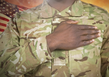Digital composite of Black soldier with right hand placed on heart for independence day