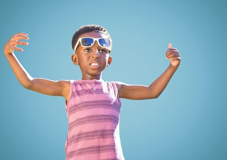 Digital composite of Boy in sunglasses hands out against blue background Stock Photo
