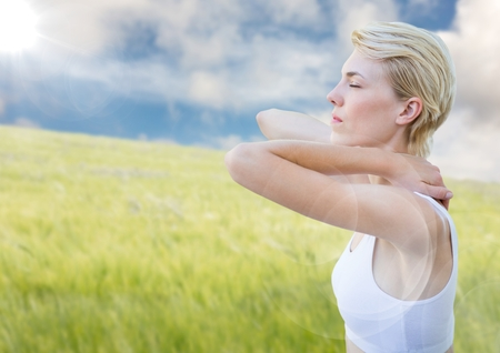 Digital composite of Woman stretching against blurry meadow on summer day with flare