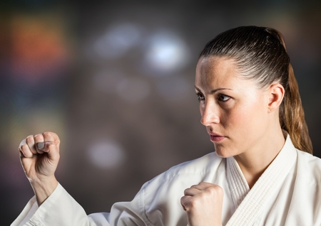 Digital composite of Woman in karate suit posing against blurry brown background Stock Photo
