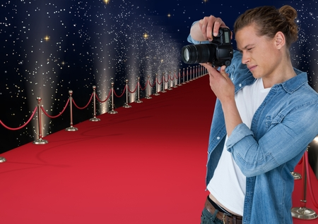 Digital composite of photographer taking a photo  in the red carpet. Lights and stars back