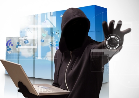 Digital composite of Hacker holding a laptop and  tendering his arm in a data center Stock Photo