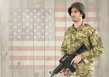 Digital composite of Proud soldier holding firearm against american flag