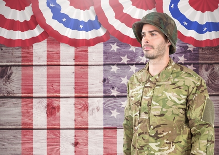 Digital composite of Soldier standing against american flag background