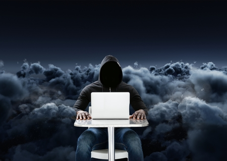 stealer: Digital composite of Hacker using a laptop in front of 3d cloudy black background