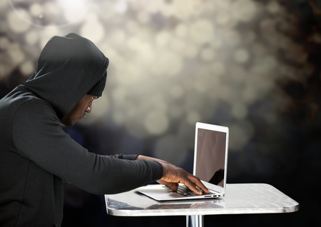 Digital composite of Side view of hacker using a laptop in front of black background Stock Photo