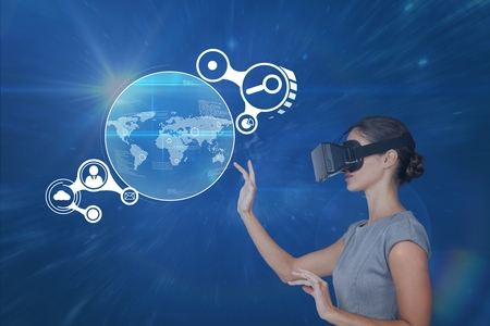 Digital composite of Woman in VR headset touching interface against blue background with flares Stock Photo