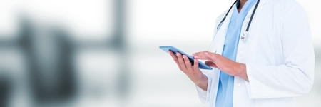 Digital composite of Doctor mid section holding tablet against blurry grey office