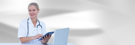 Digital composite of Doctor at computer with tablet against white blurred abstract background Stock Photo