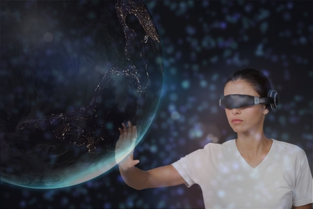 Digital composite of Woman in VR headset touching 3D planet against black background with green and purple flares