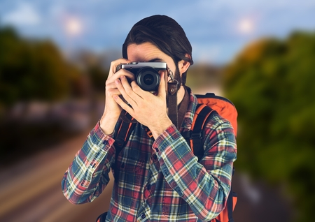 way out: Digital composite of Millennial backpacker with camera against blurry road