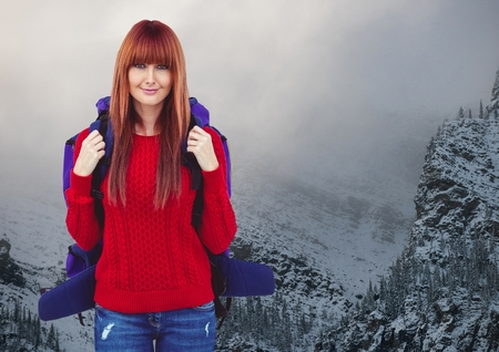 Digital composite of Millennial backpacker smiling against snowy mountains