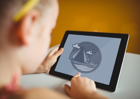 Digital composite of Girl using a tablet with travel icon on the screen Standard-Bild
