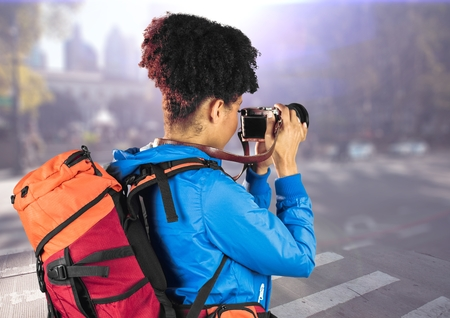 Digital composite of Millennial backpacker with camera against blurry street with flare