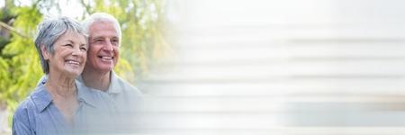 Digitale composiet van Oudere paar glimlachen buiten en wazige witte overgang