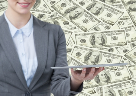 female likeness: Digital composite of Business woman mid section with tablet against money backdrop