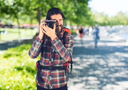 Digital composite of Millennial backpacker with camera against blurry campus