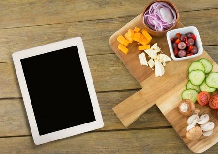 halved  half: Digital composite of Tablet on wooden desk with food 3d