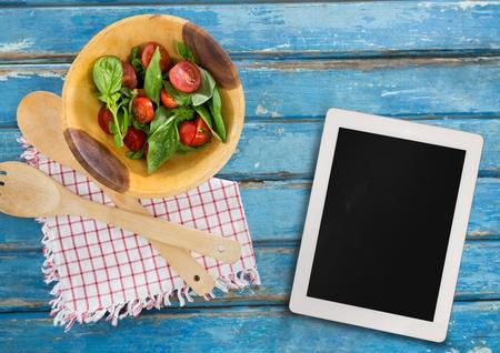 halved  half: Digital composite of Tablet on blue wooden desk with food 3d Stock Photo