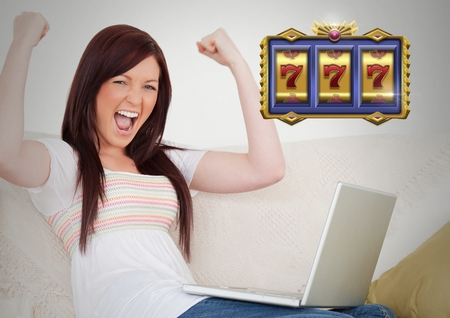Digital composite of Casino slot machine 7s in front of woman celebrating playing on laptop computer